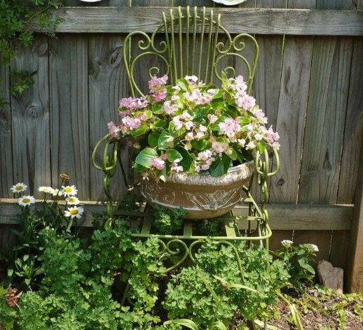 a green and gold antique chair placed in front of a brown fence with a beige flower pot with pink flowers sitting on it