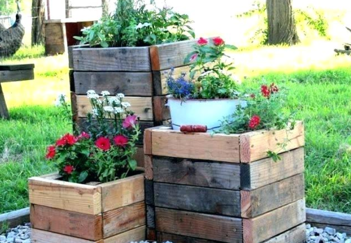 three brown wooden crates placed in a triangle with red and white flowers coming out of each one