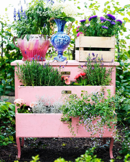 a pink dresser with open drawers placed in the garden and filled with all sorts of flowers and jars