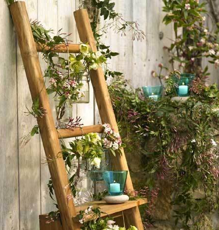 a brown ladder standing against a white wooden wall with jar planters and candles on each step