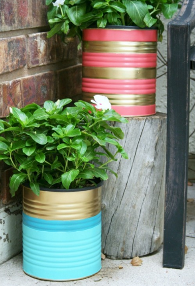 a blue and gold striped paint can and pink and gold striped paint can with green leaves coming out of them