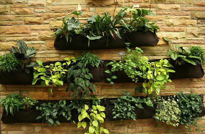 three rows of black pouch pocket planters that are nailed to a gold brick wall