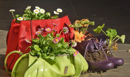 a red purse and a green purse with white and purples flowers hanging out of them
