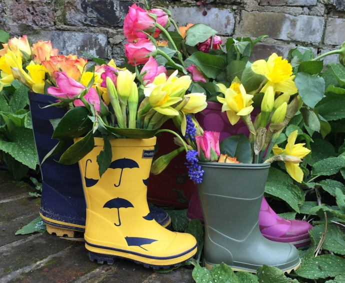 several rain boot planters with pink and yellow flowers coming out of each one