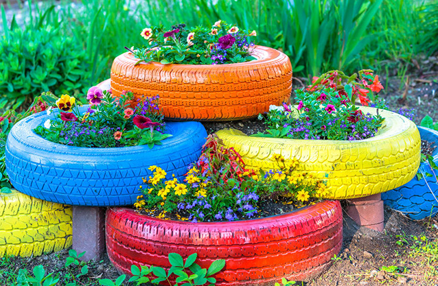 six different tire planters placed on top of each other with plants and flowers in each one