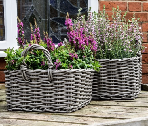 two wicker basket planters with purple and green flowers in it sitting on a brown wooden table
