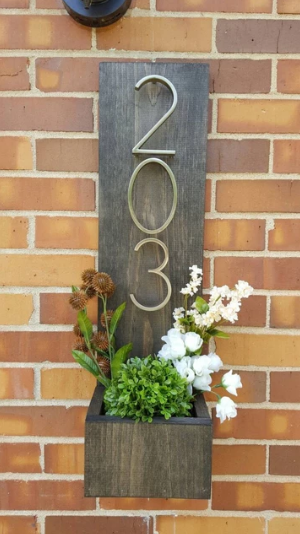 a 203 numbered address hooked onto a brown brick wall with white and green flowers in the pocket