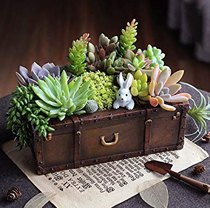 a brown briefcase placed on a desk with plants on top of it
