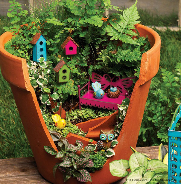 a orange broken garden pot with green leaves and small toy wooden bird houses inside