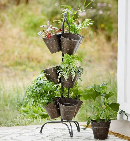 several gray bucket planters hanging from a hanger stand outside on a back porch