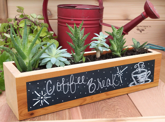 a chalkboard box planter with green and white flowers sticking out of it and a red watering can behind it