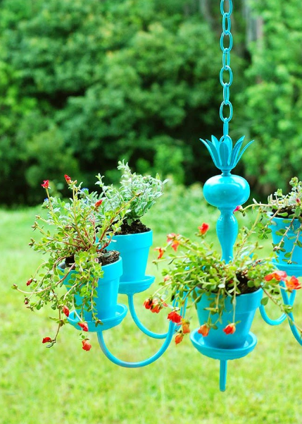 a blue chandelier hanging from a blue chain with plants in each part of it with green trees in the background