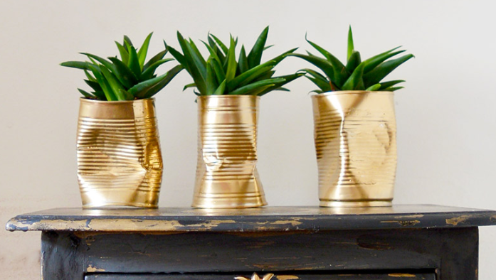 three crushed golden tin can planters on a black night stand