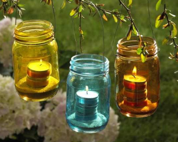 Three jars with candles in them that are blue yellow and orange in color.