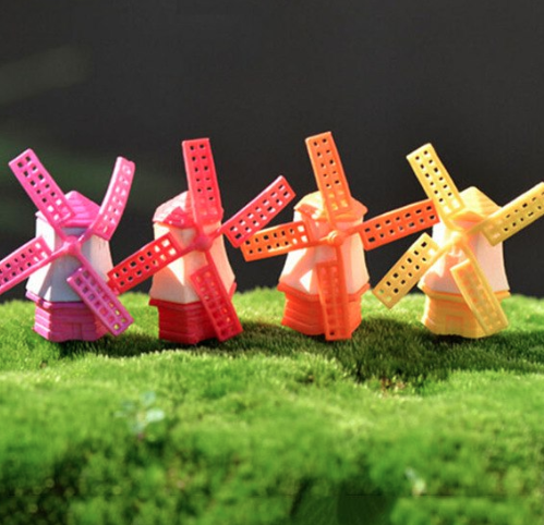 Four tiny colorful windmills resting on grass.