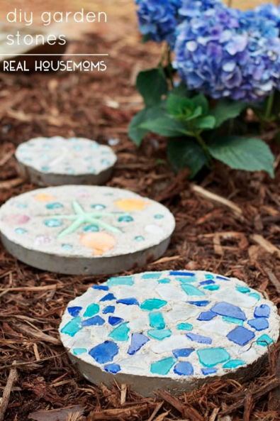 Three garden stepping stones made out of concrete with colorful shards in them.