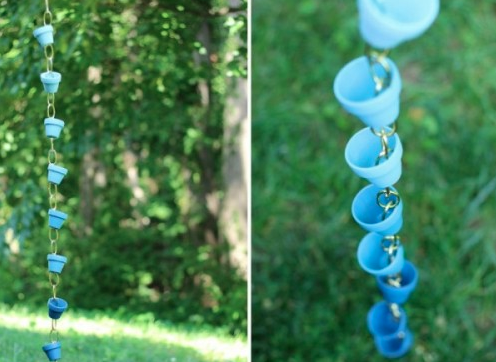 A hanging chain made of small blue planter buckets swinging from a tree branch.