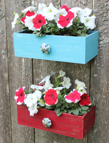 one red drawer and one blue drawer filled with flowers hanging on a wall