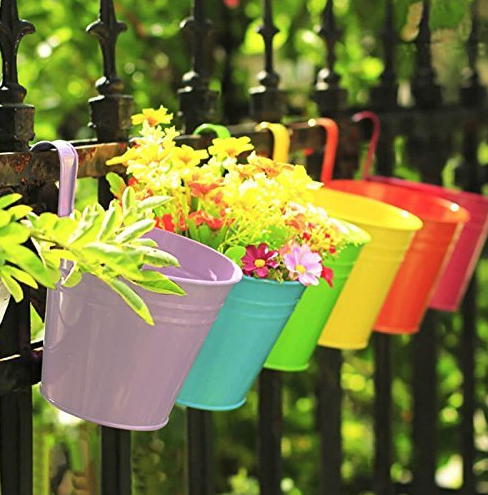 six flower buckets attached to a black fence with yellow flowers sticking out of them