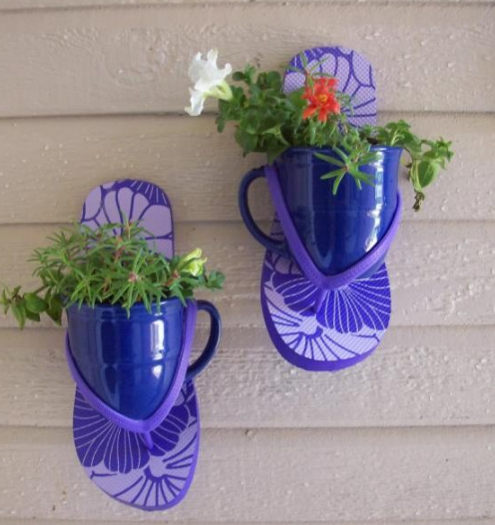 a pair of blue flip flops nailed to the wall with flowers coming out