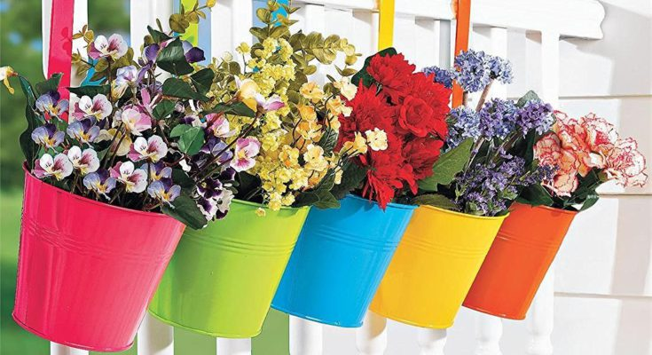 colorful bucket planters hanging on a white wooden fence