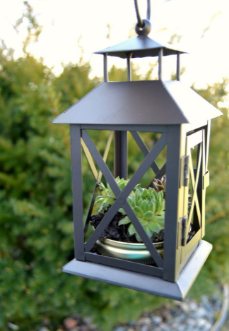 a gray lantern planter hanging by a chain in front of green trees