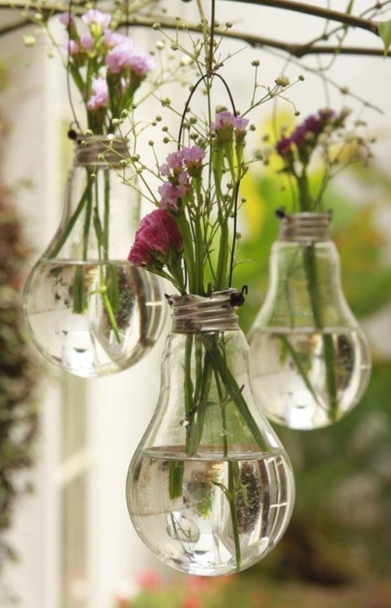 three light bulbs with purple flowers sticking out and each one is hanging from a branch