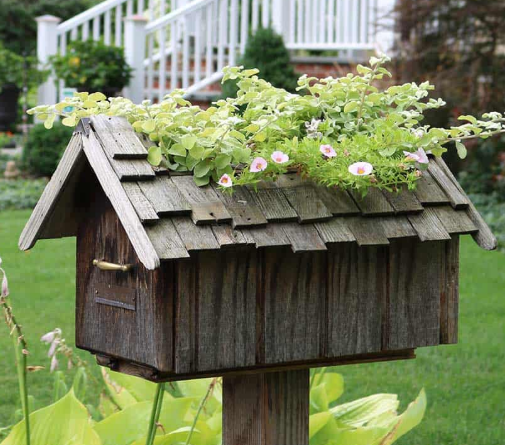 a mailbox made out of a wood with green flowers on it