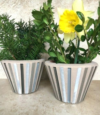 two mosaic pot planters placed beside each other on a silver table
