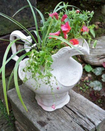 a white pitcher placed on a wooden stand with green and pink flowers coming out of it