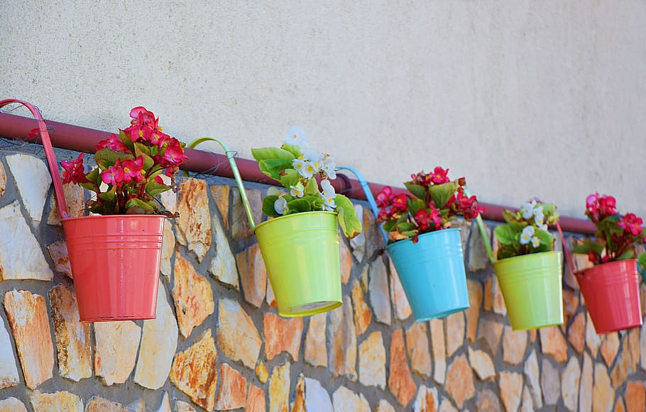 five bucket planters hanging from a pink stair rail with a brick wall behind them