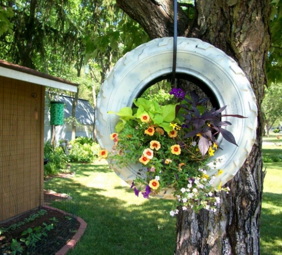 a white tire swing with flowers inside it hung from a brown tree