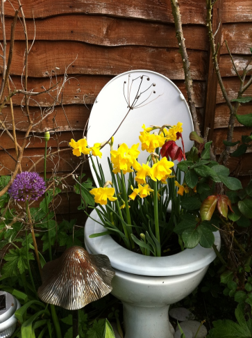 a white toilet planter placed in a garden with yellow flowers sticking out of it