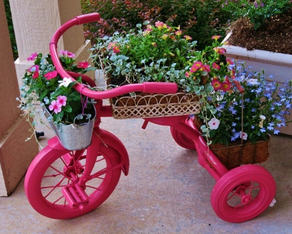 a pink toy tricycle placed on cement with green planters on it