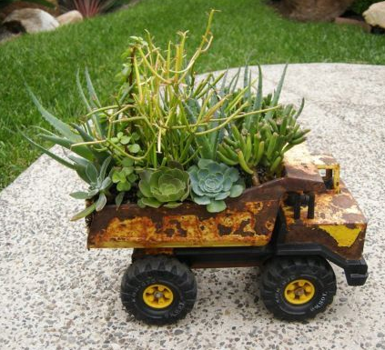 a beat up yellow toy truck filled with green plants