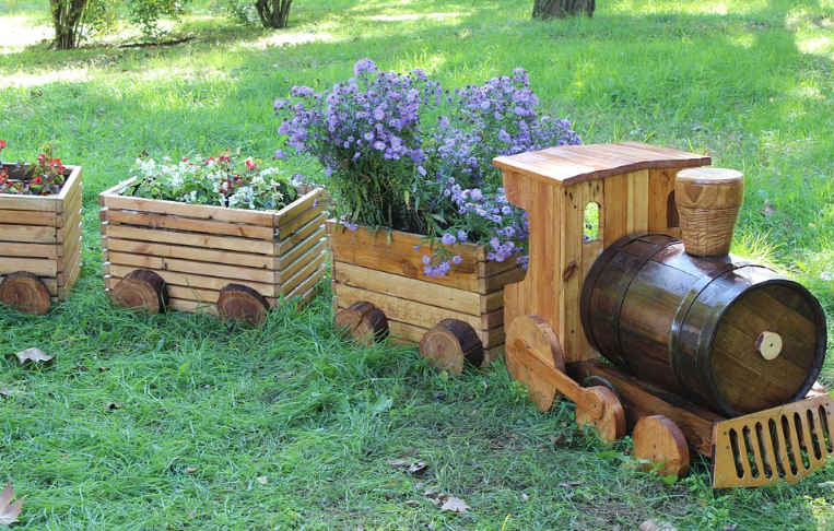 a wooden train laying on green grass with purple flowers in it