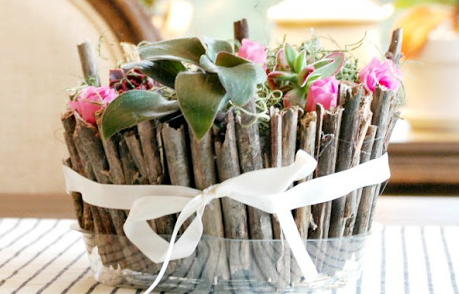 a twig planter placed on a table with a white bow wrapped around it