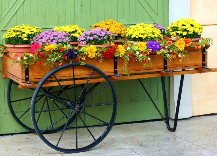 a brown planter wagon placed in front of a green barn door