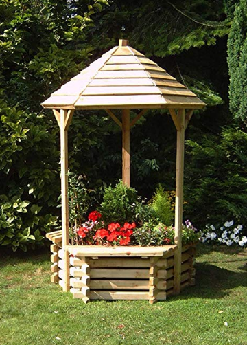a large wooden wishing well placed on grass with flowers coming out of it