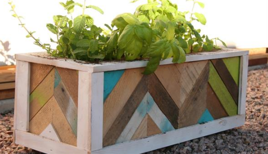 a wood chevron planter box placed on small rocks in a backyard