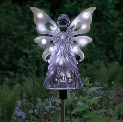 A lit up purple adult angel decoration pegged into the ground.