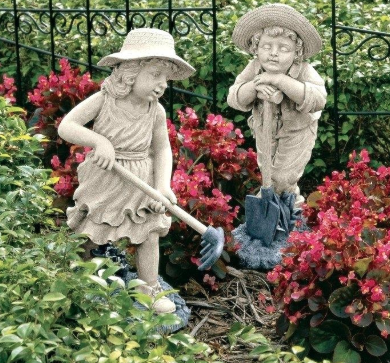 Two stone sculptures of a little boy and little girl digging with shovels placed on garden soil