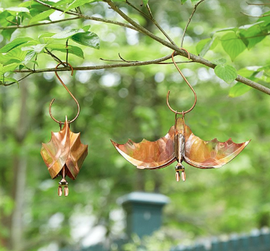 Two bronze bat ornaments dangling from a tree branch with leaves in the background