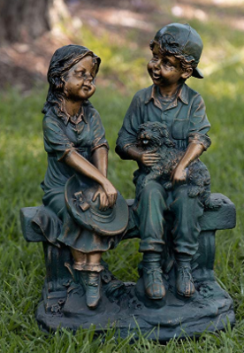 A statue of small girl and boy sitting on a bench.
