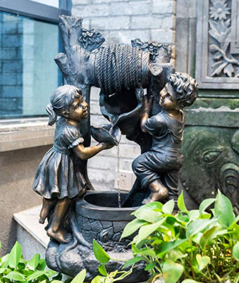 A small statue of a boy and girl playing with an outdoor water fountain.
