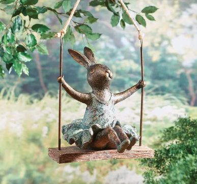 A decoration of a stone bunny on a swing hanging from a tree