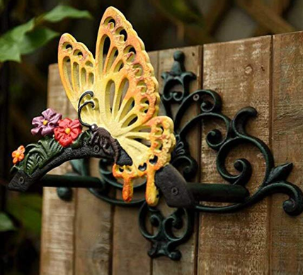 A gold elegant butterfly decoration stuck onto the top of a wooden fence