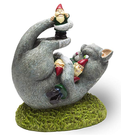 A curled up cat statue with three gnomes on top of it