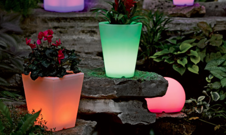 Color changing solar planters resting on large rocks