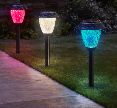 Three colorful solar lights pegged into a garden walkway